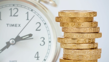 IENT103 Course Image: Image compilation showing stack of gold coins in the foreground with faded clock face in the background